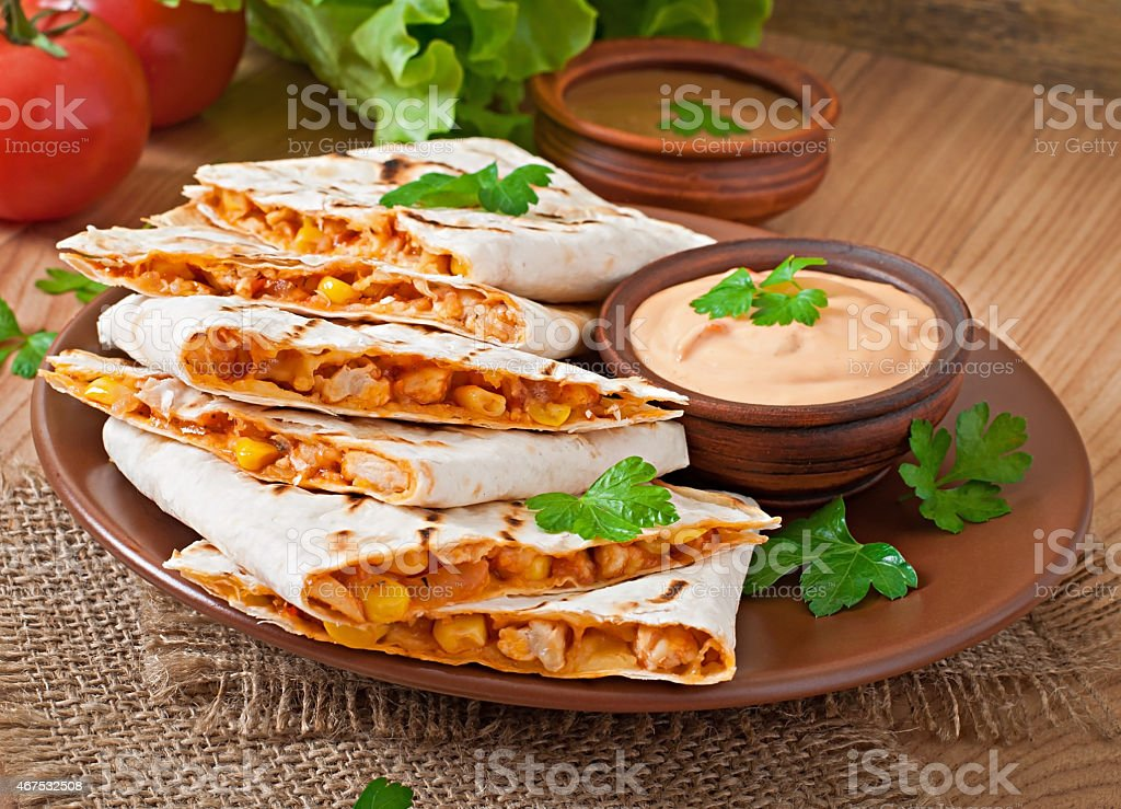 Mexican Quesadilla sliced with vegetables and sauces stock photo
