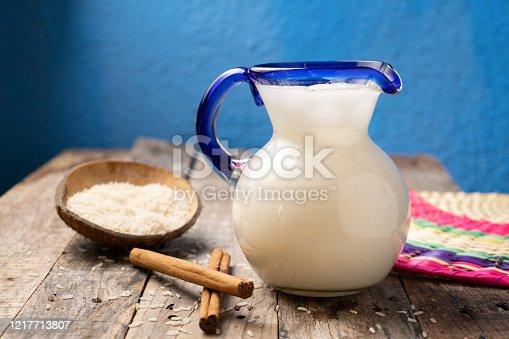 Traditional mexican rice horchata with cinnamon on wooden background