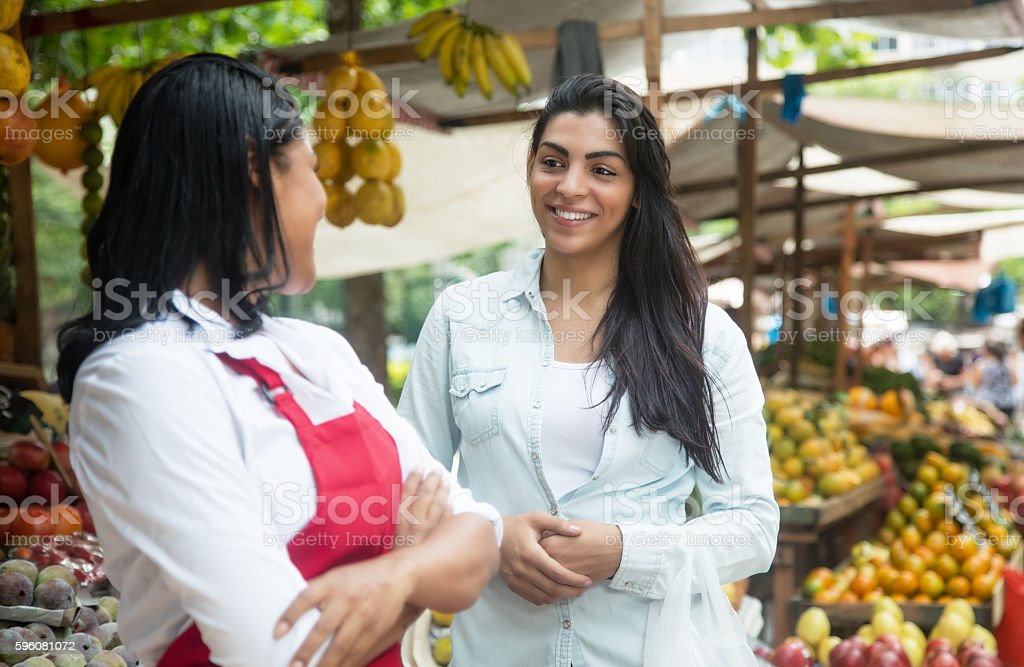 Mexican saleswoman on a farmers market talking with client royalty-free stock photo