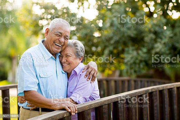 A mexican senior couple laughing together on bridge.
