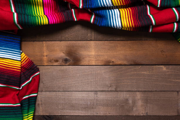 Mexican Serape blanket on wood Background A mexican serape blanket on a wooden plank background mexican culture stock pictures, royalty-free photos & images