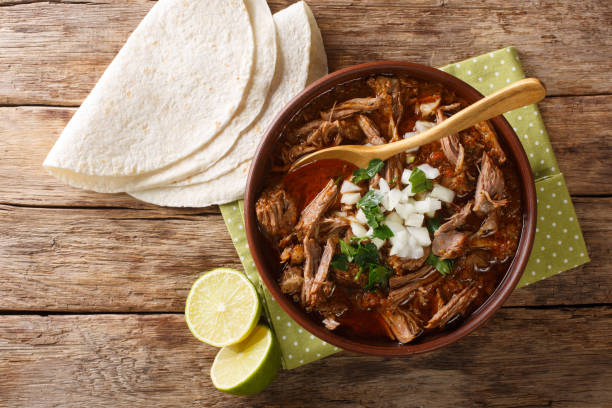 Mexican style slow cooked beef stew Birria de Res served with lime and tortilla closeup in a bowl. Horizontal top view stock photo