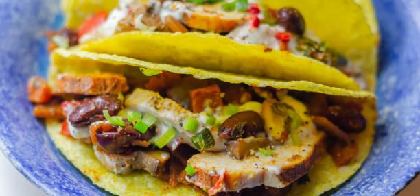 Tacos mexicanos conchas com frango e feijão de rim vermelho, cebola, pimentas vermelhas e verdes, e molho de salsa - foto de acervo