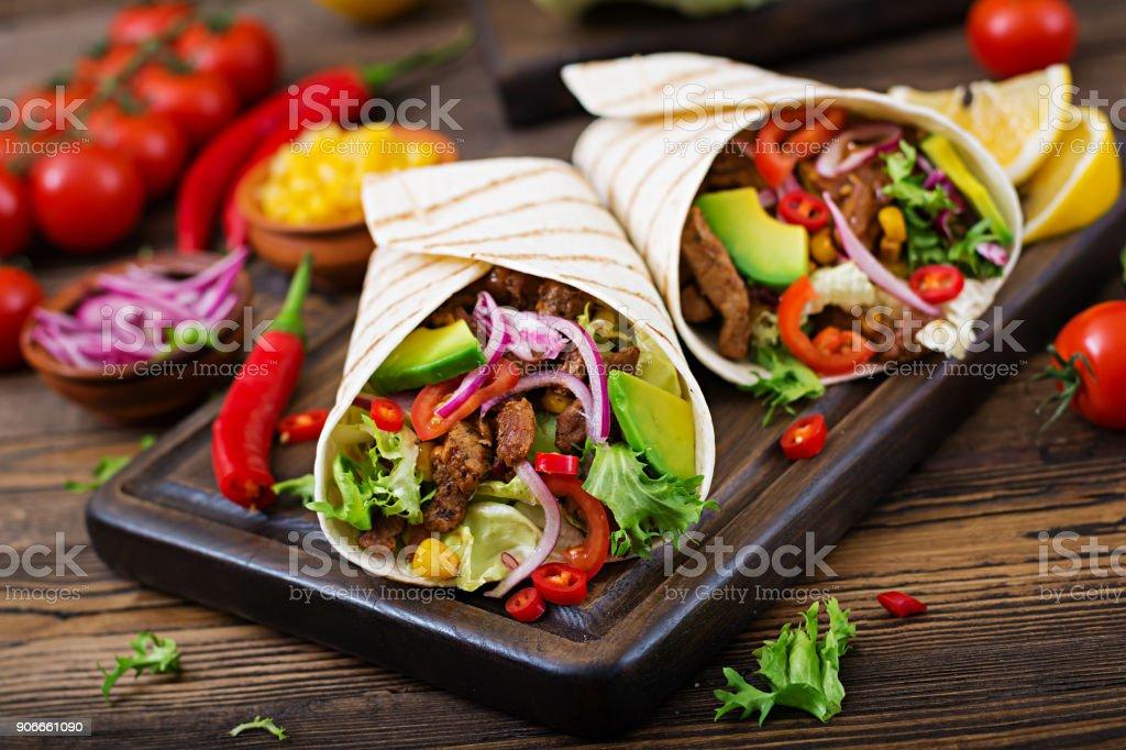 Mexikanische Tacos mit Rindfleisch in Tomaten-Sauce und Avocado-salsa – Foto