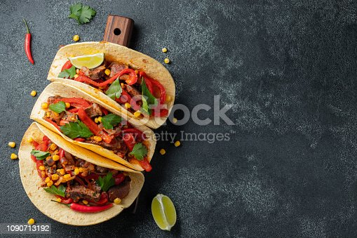 Mexican tacos with beef, vegetables and salsa. Tacos al pastor on wooden board on black background. Top view with copy space.