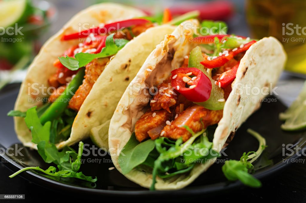 Mexican tacos with chicken fillet in tomato sauce and salsa of paprika and arugula royalty-free stock photo