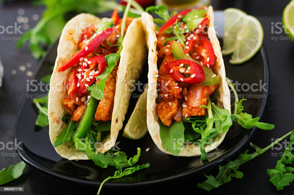 Mexican tacos with chicken fillet in tomato sauce and salsa of paprika and arugula photo libre de droits