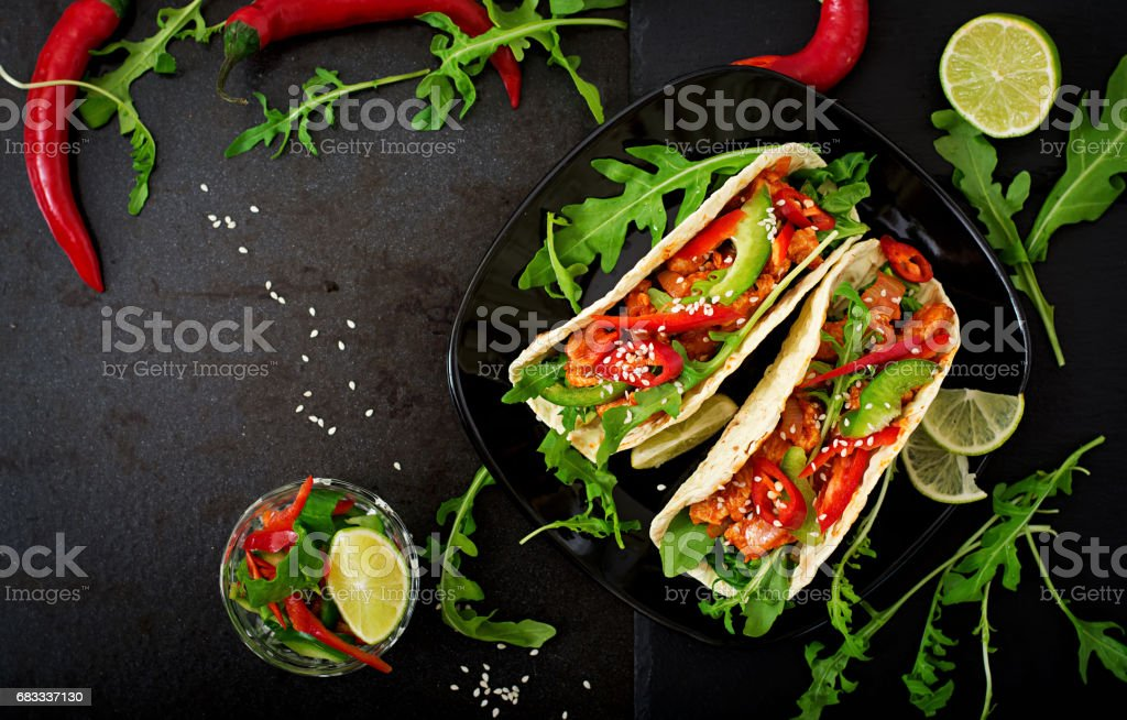 Mexican tacos with chicken fillet in tomato sauce and salsa of paprika and arugula. Flat lay. Top view royalty-free stock photo
