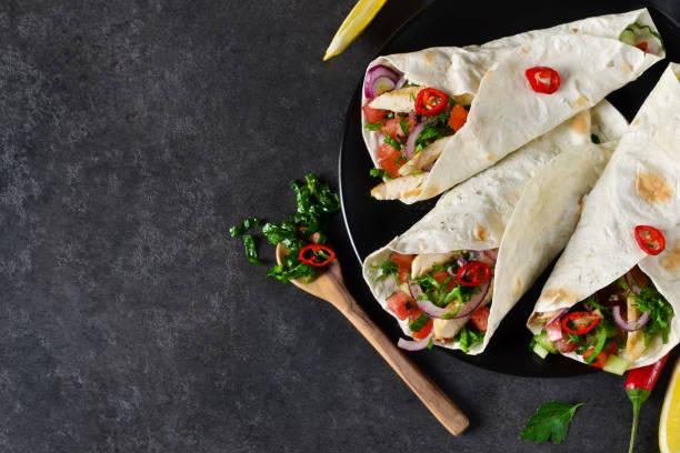 mexikanische tacos mit füllung und guacamole sauce auf schwarzem hintergrund - veggie wraps stock-fotos und bilder