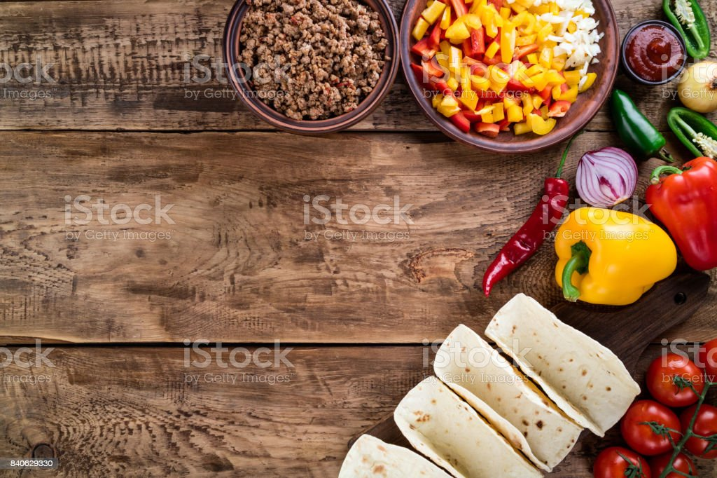 Mexican tacos with vegetables and meat. Ingredient for cooking tacos al pastor on wooden background. Top view stock photo