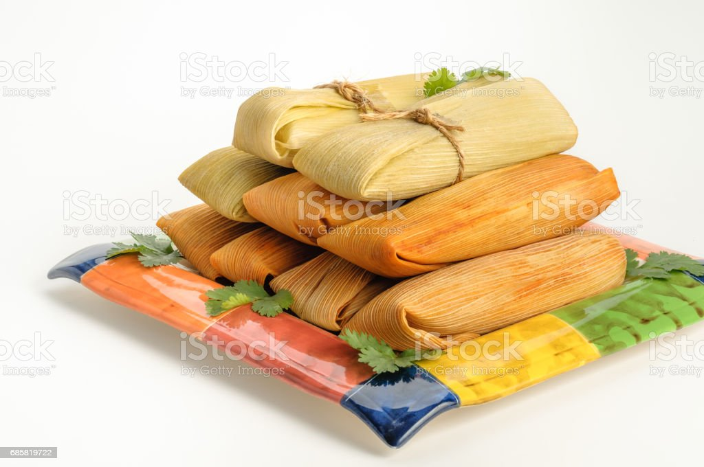 Mexican tamales made of corn and chicken isolated on white stock photo