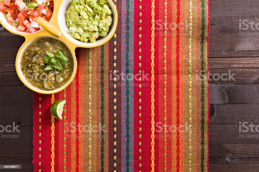 an overhead close up shot of a colorful placemat and bowls with a...