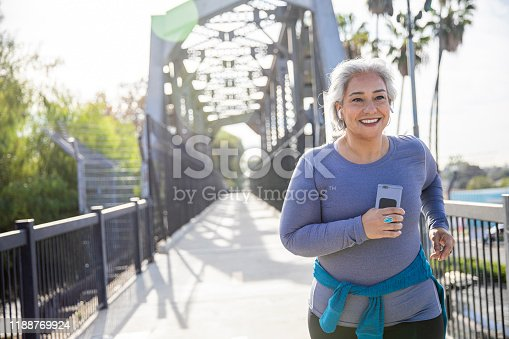 A mature Mexican woman jogging on a trail