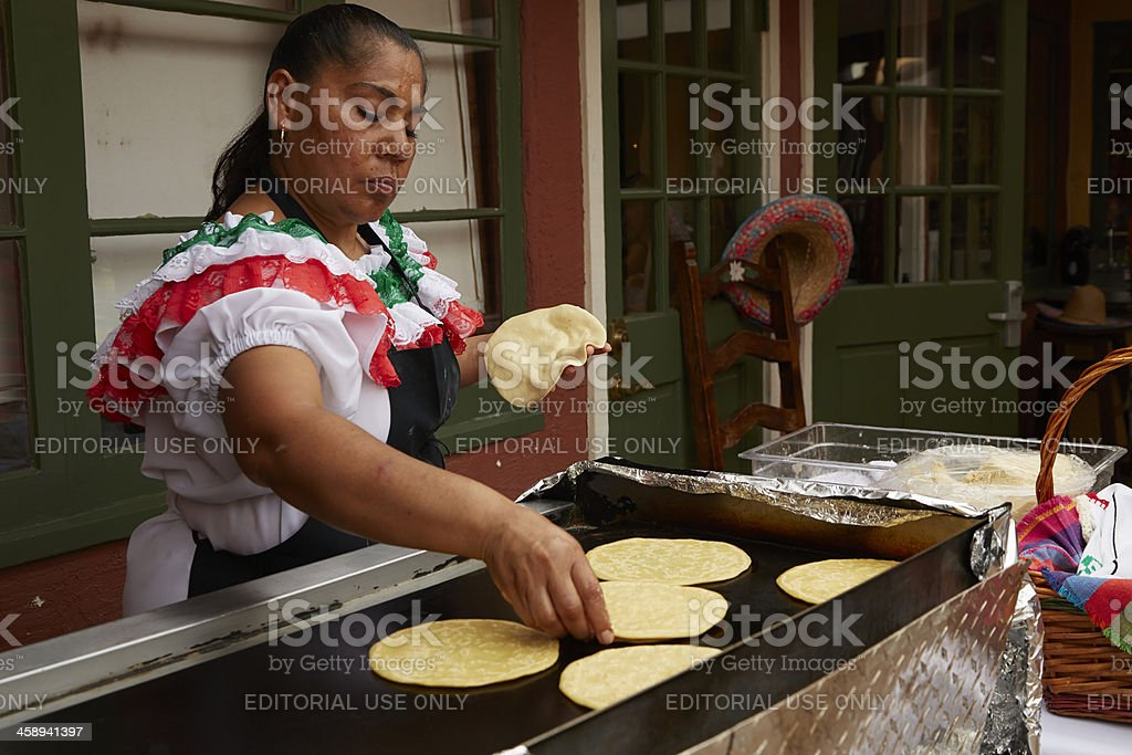 Mexican Woman Prepares Tortillas On Open Griddle stock photo