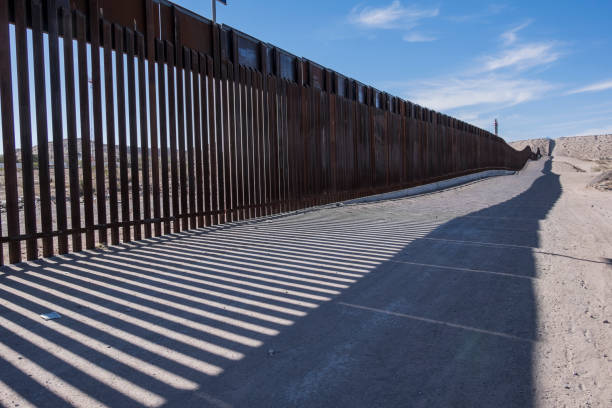 US Mexico Border Fence The border fence between New Mexico and Mexico. Strong shadows are cast upon the dirt road on the US side of the border. international border barrier stock pictures, royalty-free photos & images