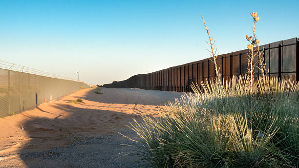 US Mexico Border in New Mexico Wide angle shot of the border between Mexico and USA with bush in the foreground and a clear blue sky at dusk geographical border stock pictures, royalty-free photos & images