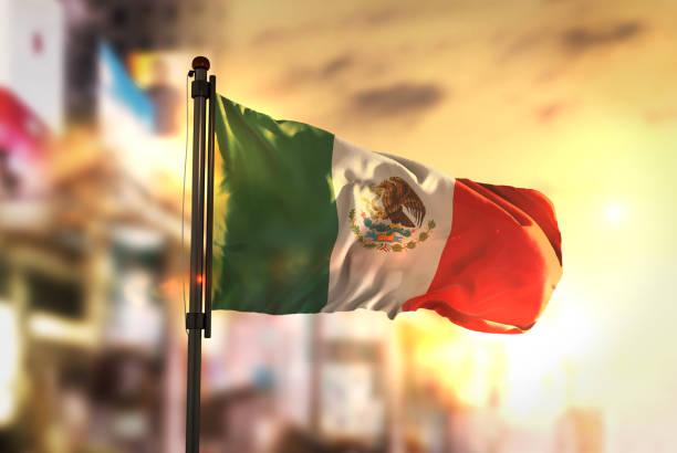 bandera de méxico contra la ciudad borrosa de fondo en contraluz amanecer - bandera mexico fotografías e imágenes de stock