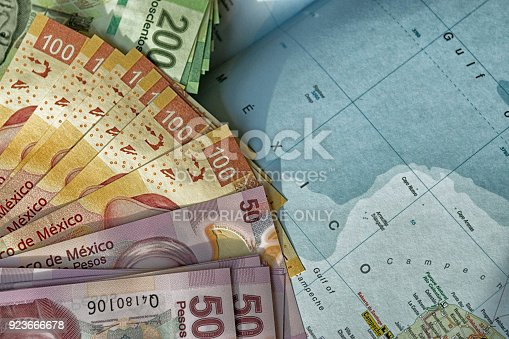 Mexican map with thousands of peso notes in several denominations ready for going on vacation. The image features bundles of new Mexican peso notes on a generic School Atlas background showing the Mexican country and the word Mexico in the Caribbean Sea.