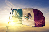 Mexico Mexican flag on flagpole textile cloth fabric waving on the top sunrise mist fog
