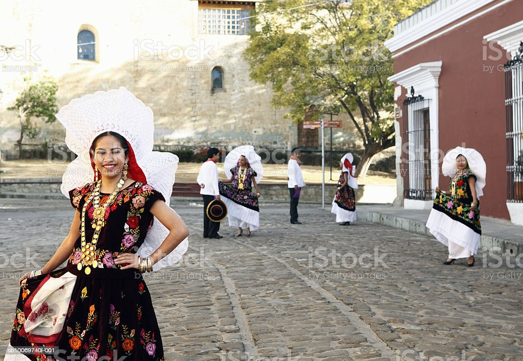 Mexico, Oaxaca, Istmo, portrait of woman in traditional costume at street, others in background foto de stock libre de derechos
