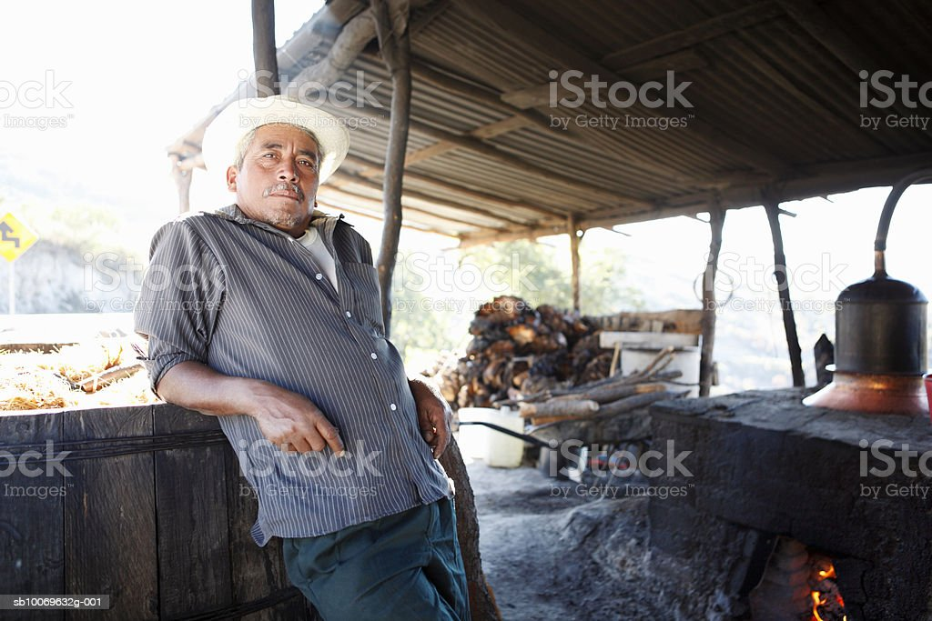 Mexico, Oaxaca, Man standing by distilling equipment under roof, portrait royalty-free stock photo