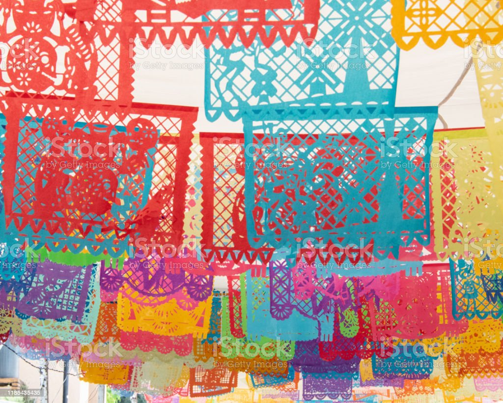 Mexico Papel Picado- Cut out paper flags, Day of the Dead, Michoacan In Mexico for the Day of the Dead celebration (dia del los muertos) in the small town of Capula outside of Patzcuaro in the state of Michoacan, the townspeople prepare for the Day of the Dead celebration.  Papel Picado (cut out paper) flyers (flags) are strung  creating a colorful and festive scene. Altar Stock Photo