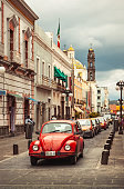 MEXICO - jule 14: beautiful view on a Mexican town with red Volkswagen Beetle vintage classic car in the foreground and a church in the background, Jule 14, 2012 Mexico