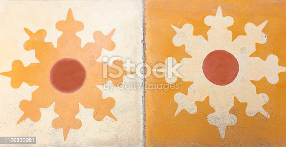 Mexico Style: Antique floor tiles with floral motif in orange and gold. Close-up shot. Shot in the Yucatan Peninsula.