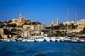 Maltese flag in front of Mgarr harbour on Gozo island on Malta.