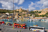 Mgarr, Gozo, Malta - October 15, 2019: Port town with sightseeing tour buses waiting for tourists at the harbour in Gozo island, northern region of Malta