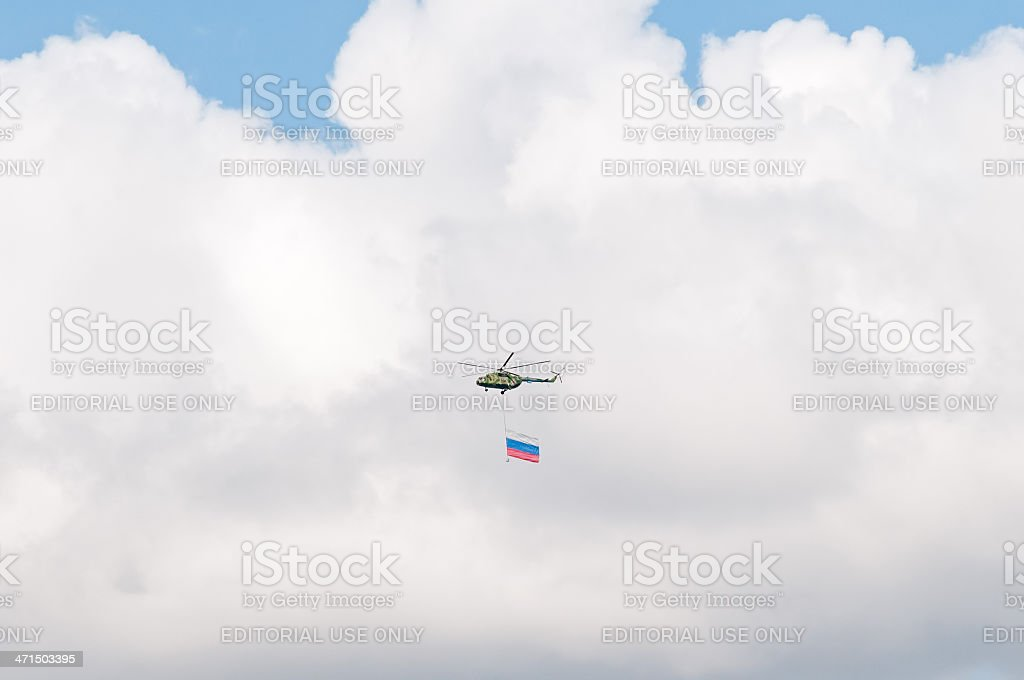 Mi-8 helicopter with giant Russian National flag against sky background royalty-free stock photo