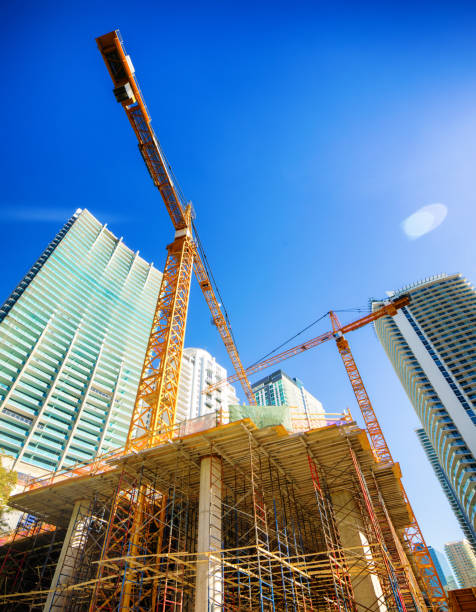 Miami Brickell modern skyscrapers under construction with cranes and lens flare stock photo