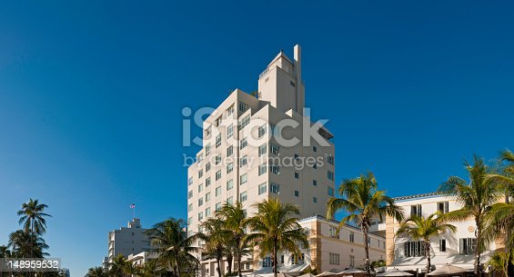 Clear blue Florida skies over the pastel colored art deco district hotels and apartment blocks, cafes, palm trees and ocean promenade of South Beach, Miami. ProPhoto RGB profile for maximum color fidelity and gamut.