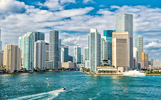 miami skyline. Yachts sail on sea water to city skyscrapers on cloudy blue sky in Miami, USA. Summer vacation, wanderlust, travelling, lifestyle concept.