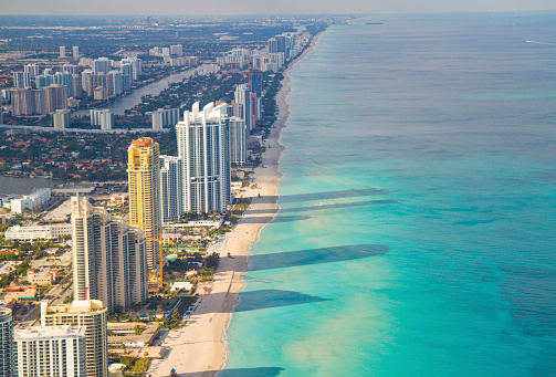 Aerial shot of Miami South Beach full of hotels with some long shadows reaching into the sea. Florida, USA.