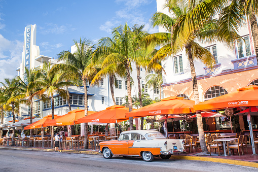 Miami Beach, Florida, USA - April 25, 2016:   View along Ocean Drive along South Beach Miami in the historic Art Deco District with hotels, restaurant, people and classic car visible.  South Beach has been  a notable tourist destinations for many years.