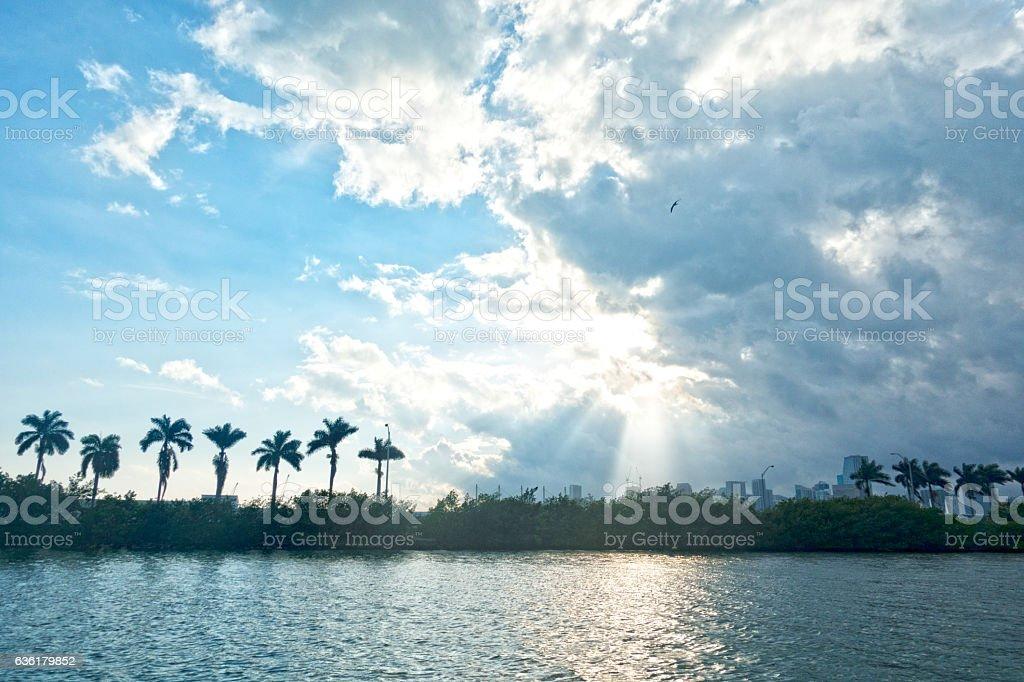Miami Sun Through Clouds Reflection on Water MacArthur Causeway stock photo