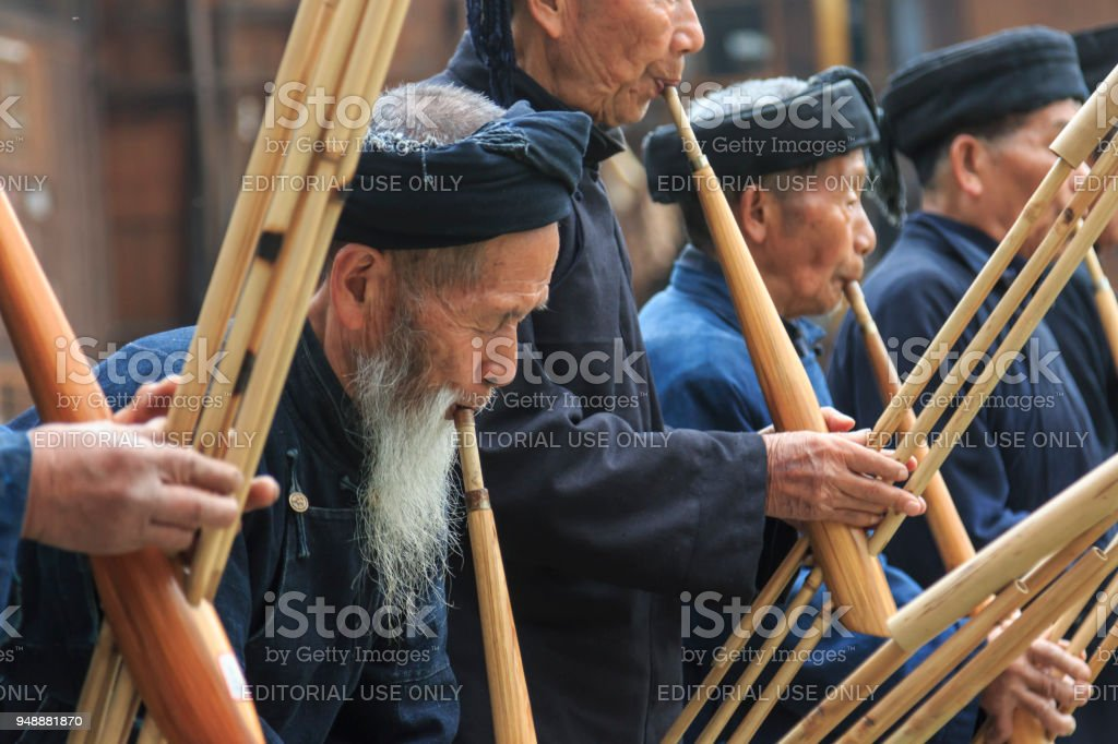 Miao men playing a traditional flute in Langde Miao village, Guizhou province, China stock photo
