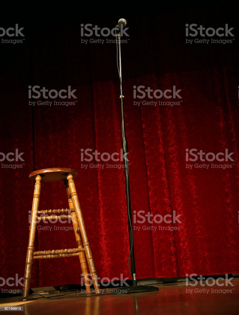 Mic stand and stool on comedy stage with red curtain stock photo