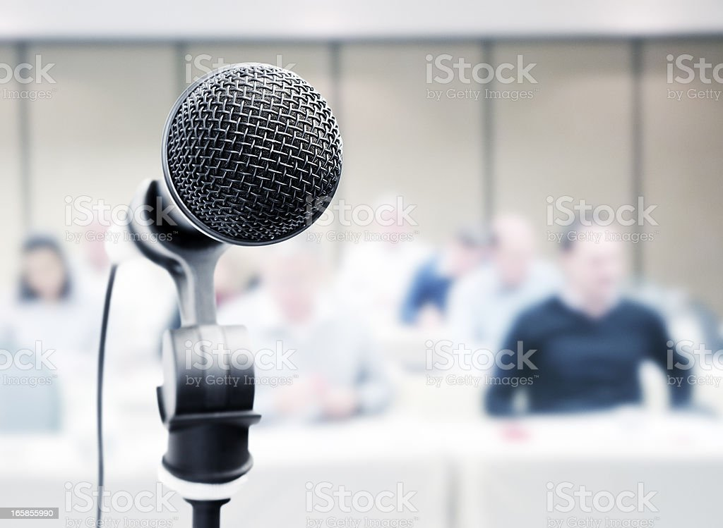 Mic stands ready in front of blurred audience royalty-free stock photo