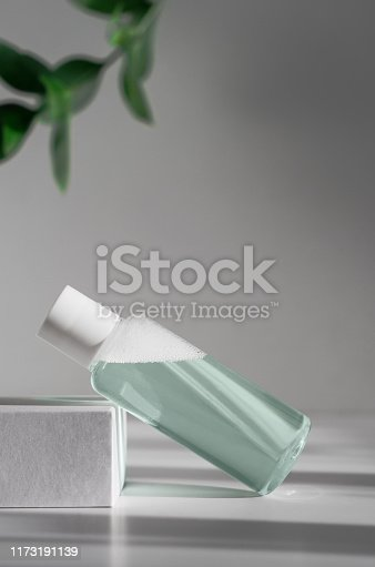 istock Micellar water, makeup remover mockup side view. Natural cosmetology product, organic cosmetics poster concept. Moisturizing lotion bottle with leaves on background. Women skin care, hygiene concept 1173191139