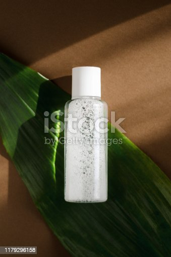 istock Micellar water, makeup remover transparent bottle mockup. Natural cosmetology liquid, organic cosmetics on green leaf background. Moisturizing lotion. Women facial skin care product 1179296158