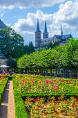 Bamberg, Germany - July 30, 2015: Michaelsberg Abbey on background and on rose garden on foreground. People on background. Michaelsberg Abbey Bamberg is a former Benedictine monastery in Bamberg in Bavaria, Germany. After its dissolution in 1803 the buildings were used for the almshouse Vereinigte Katharinen- und Elisabethen-Spital, which is still there as an old people's home.