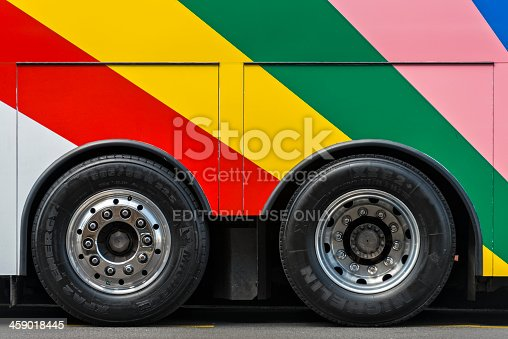 Auckland, New Zealand - February 22, 2013: A bus standing on an Auckland city street has large sized Michelin tires and a very colorful chassis.