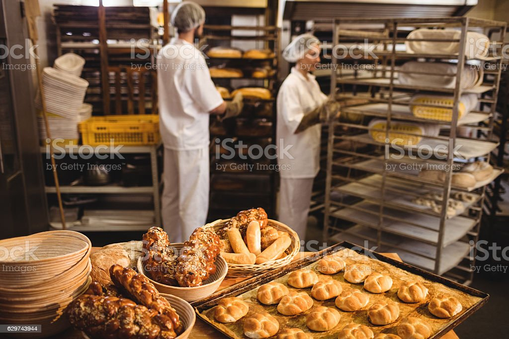 Michetta and sweet food on a table while bakers working – Foto