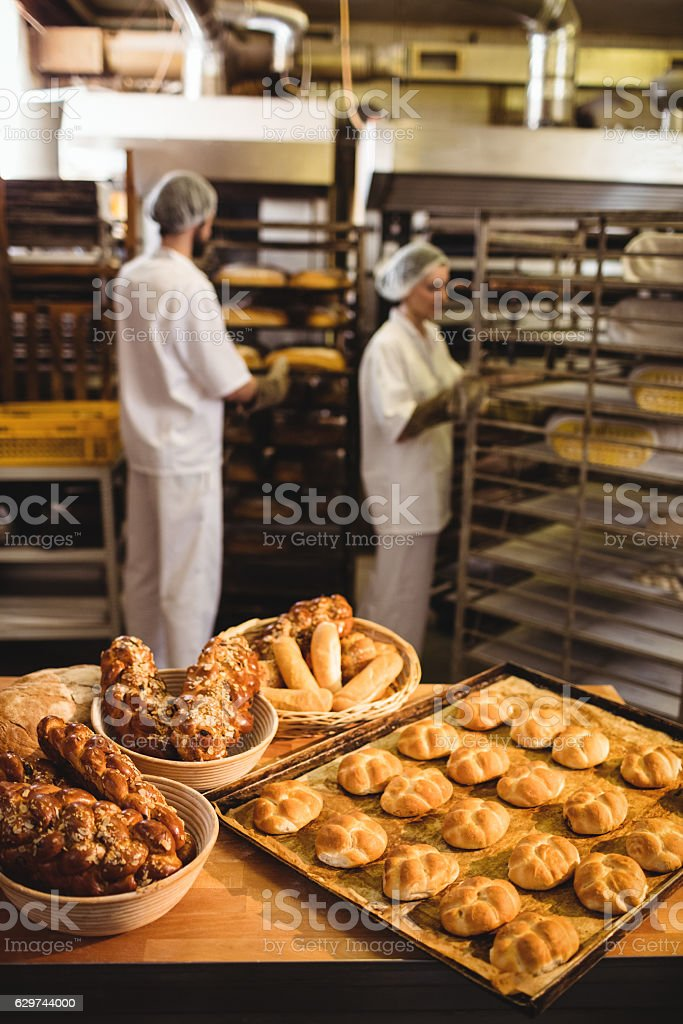 Michetta and sweet food on a table while bakers working stock photo