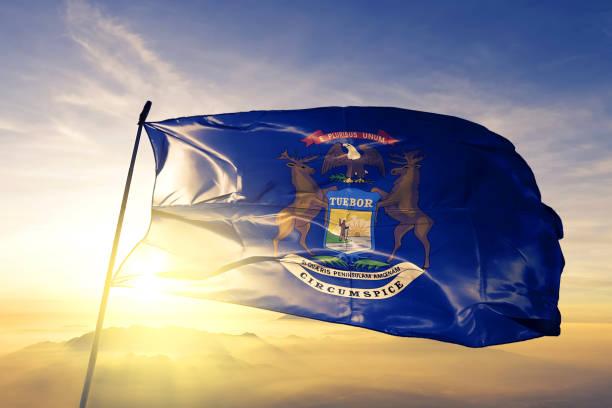 michigan staat van de verenigde staten vlag doek textielweefsel zwaaien op de bovenste zonsopgang mist mist - michigan stockfoto's en -beelden