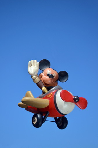 Monchique, Faro - Portugal, 17, April 2013. Studio image of a Mickey Mouse resin figure with a sky background.  Mickey is flying his plane while waving to his fans. Mickey is part of a huge private collection of resin big figs that were sold in selective stores around the world.  Mickey mouse was created by Walt Disney in 1928 Photo taken April 17th, 2013