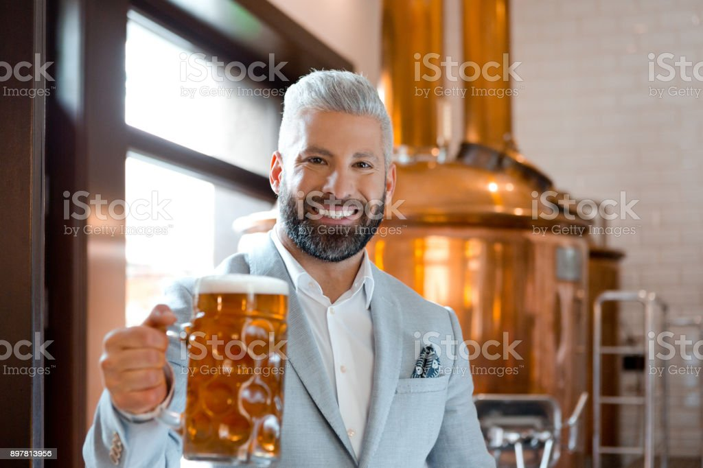Micro brewery owner with a mug of fresh beer Elegant microbrewery owner with a mug of beer in his pub. Handsome brewery owner with a glass of fresh beer. Adult Stock Photo