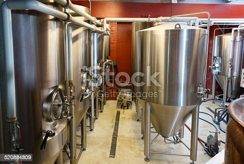 Rows of stainless steel fermenting vessels containing various types of beer from lager pilsners to stouts photographed in a small boutique brewery in Denmark.